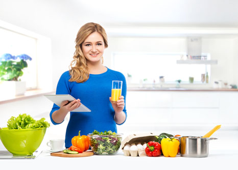 Women with nutritious food in kitchen